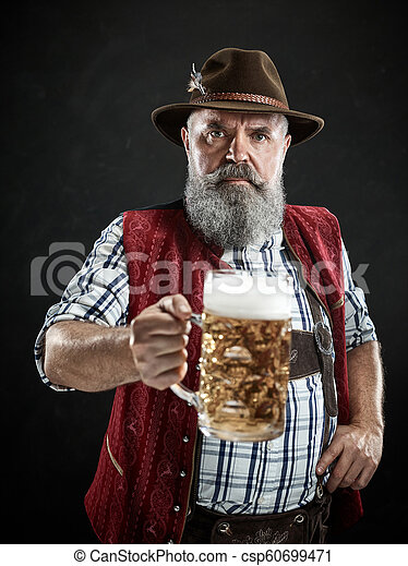 Germany, Bavaria, Upper Bavaria, man with beer dressed in in traditional Austrian or Bavarian costume - csp60699471