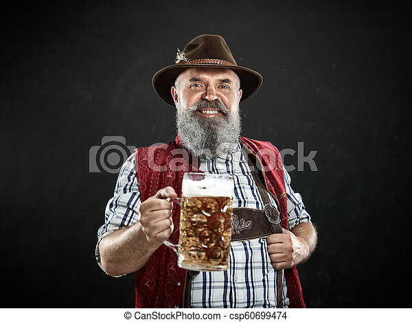 Germany, Bavaria, Upper Bavaria, man with beer dressed in in traditional Austrian or Bavarian costume - csp60699474