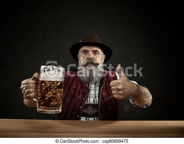 Germany, Bavaria, Upper Bavaria, man with beer dressed in in traditional Austrian or Bavarian costume - csp60699475