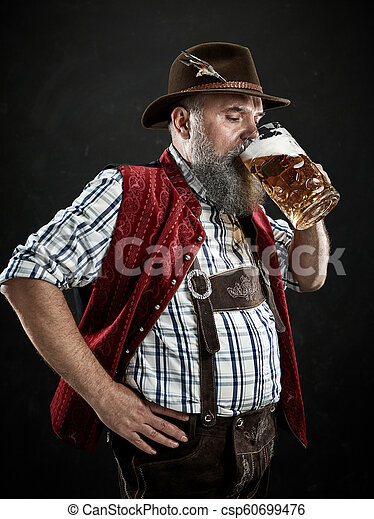 Germany, Bavaria, Upper Bavaria, man with beer dressed in in traditional Austrian or Bavarian costume - csp60699476