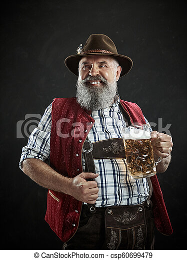 Germany, Bavaria, Upper Bavaria, man with beer dressed in in traditional Austrian or Bavarian costume - csp60699479