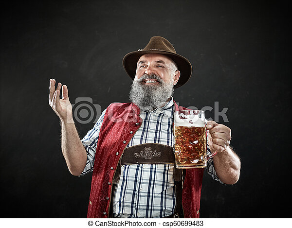 Germany, Bavaria, Upper Bavaria, man with beer dressed in in traditional Austrian or Bavarian costume - csp60699483