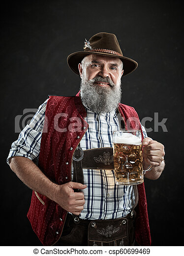 Germany, Bavaria, Upper Bavaria, man with beer dressed in in traditional Austrian or Bavarian costume - csp60699469
