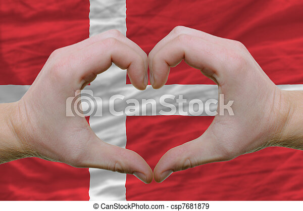 Gesture made by hands showing symbol of heart and love over denmark flag - csp7681879