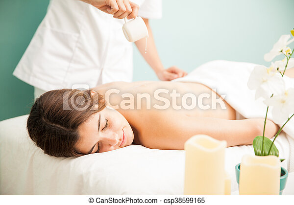 Getting a candle massage at the spa - csp38599165