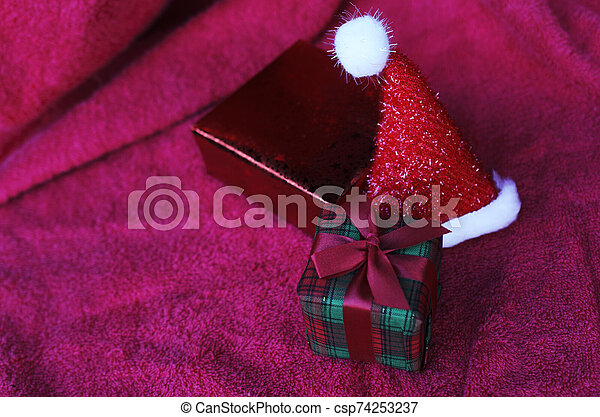 Gift box and christmas hat with macro close up on red carpet backgrounds - csp74253237