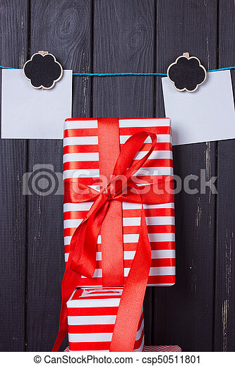 Gift box with a red bow on a wooden background - csp50511801