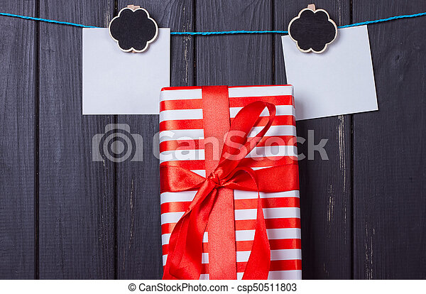 Gift box with a red bow on a wooden background - csp50511803