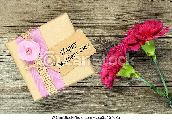 Gift box with Happy Mothers Day tag and carnations against rustic wood - csp35457625