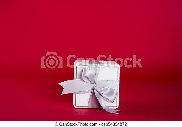 Gift box with silver ribbon bow - csp54354872