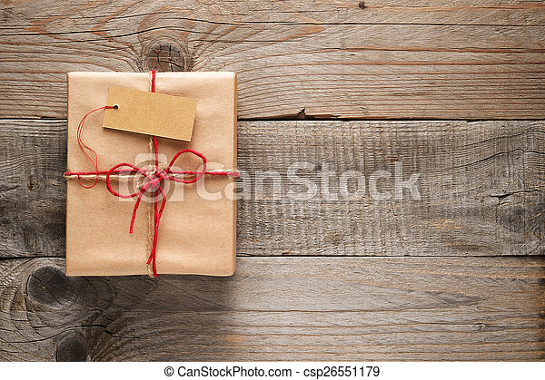 Gift box with tag on wooden background - csp26551179