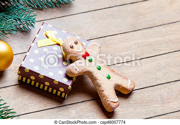 gift, gingerbread man and fir tree branch with bauble on the wonderful brown wooden background - csp46007774