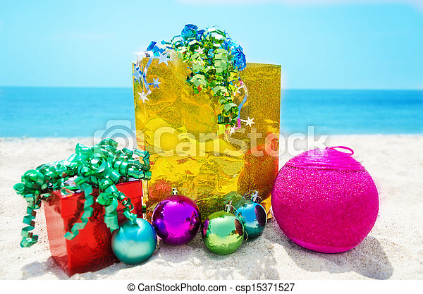 Gifts with Christmas ball on the beach - csp15371527