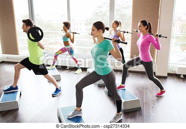 Un grupo de gente haciendo ejercicio con Barbilla en el gimnasio - csp27314334