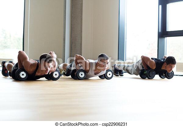 Un grupo de hombres con pesas en el gimnasio - csp22906231