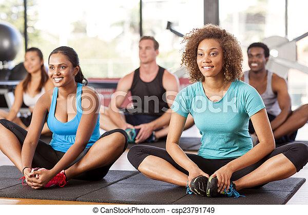Grupo multiétnico extendiéndose en un gimnasio - csp23791749