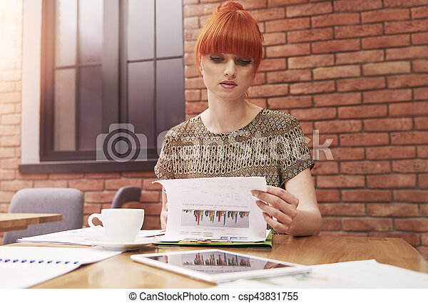 Ginger woman with stack of business documents - csp43831755