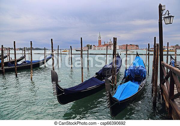 Gondolas y San Giorgio Maggiore Island en Venecia, Italia - csp66390692