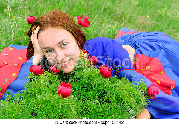 gipsy girl in blue, lying on green grass with a flower - csp4154442