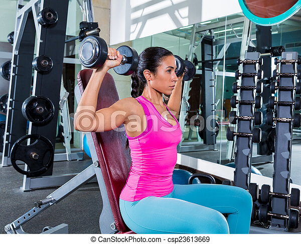 girl at gym seated dumbbell shoulder press - csp23613669