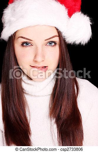 cfe24757e63f1 Girl biting her lip wearing santa hat. A flirtatious young woman ...