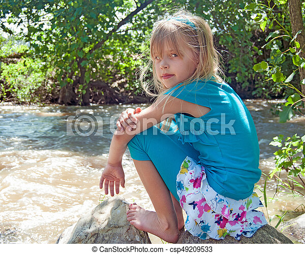 girl by river on a rock - csp49209533