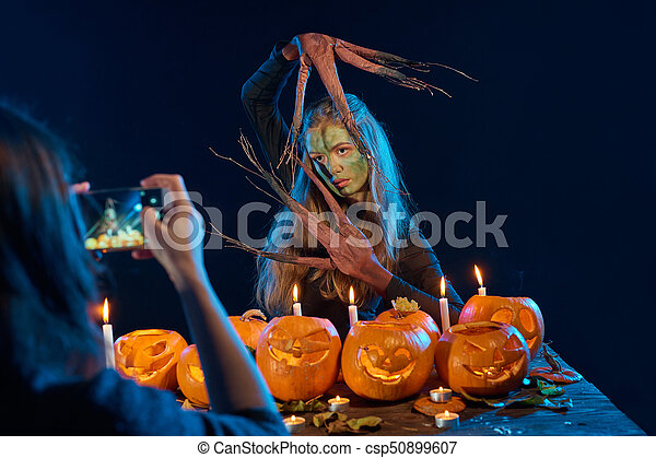 Girl capturing photo of Halloween woman with her smart phone - csp50899607