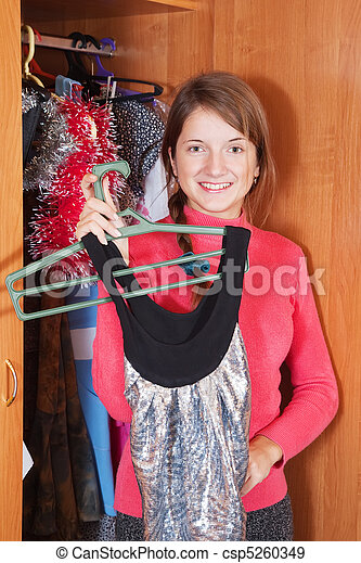 Girl chooses dress in wardrobe - csp5260349