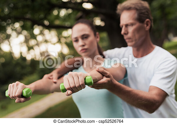 Girl doing exercises with dumbbells in the park. A man helps her. They are smiling - csp52526764