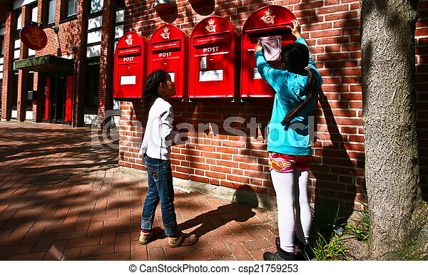 girl dropping a letter in a red postbox in denmark - csp21759253