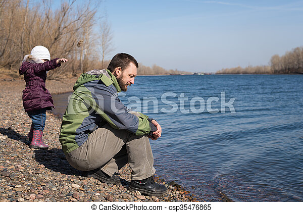 Girl dropping a stone into river - csp35476865