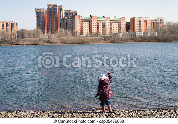 Girl dropping stones into river - csp35476860