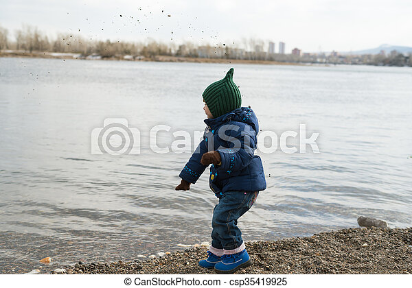 Girl dropping stones into the river - csp35419925