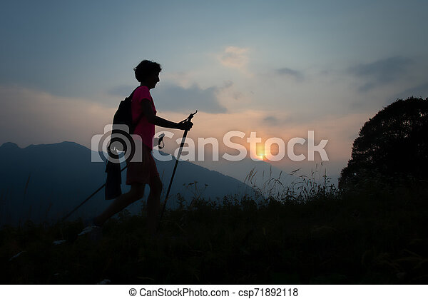 Girl during a sunset evening trek in the hills - csp71892118