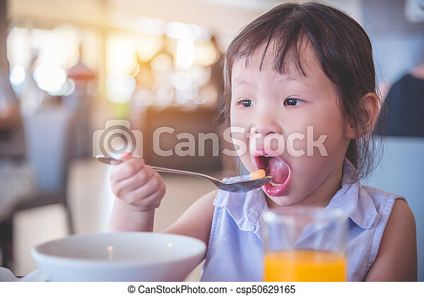 girl eating cereal for breakfast - csp50629165