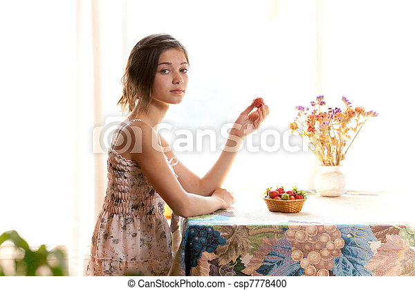 Girl eating strawberries sitting at table indoor in summer day - csp7778400