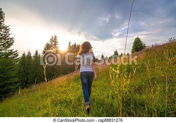 Girl enjoy pure nature. Walk over the field to meet sunset - csp88831276