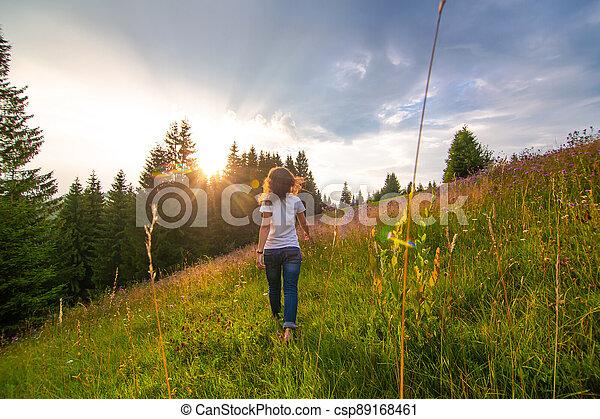 Girl enjoy pure nature. Walk over the field to meet sunset - csp89168461