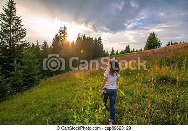 Girl enjoy pure nature. Walk over the field to meet sunset - csp89623129