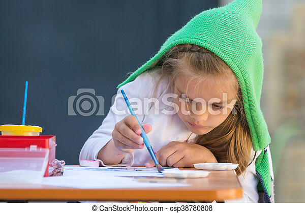 Girl enthusiastically paints watercolors sitting at a table in the yard - csp38780808