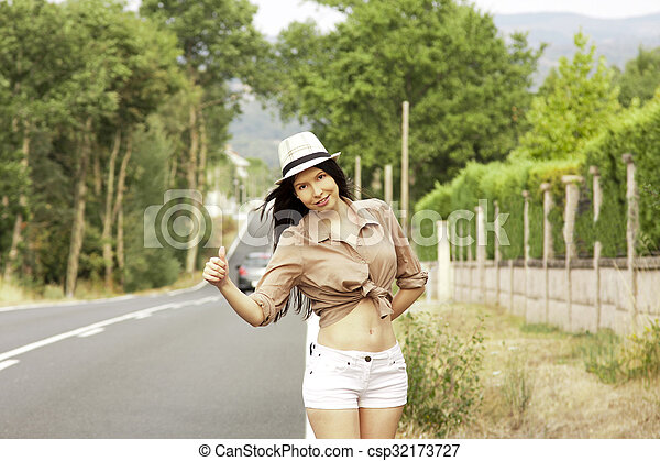 girl hitchhiking on the road - csp32173727