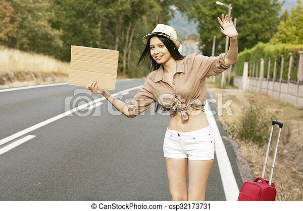 girl hitchhiking on the road - csp32173731