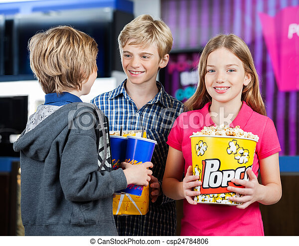 Girl Holding Popcorn While Brothers Talking At Cinema - csp24784806