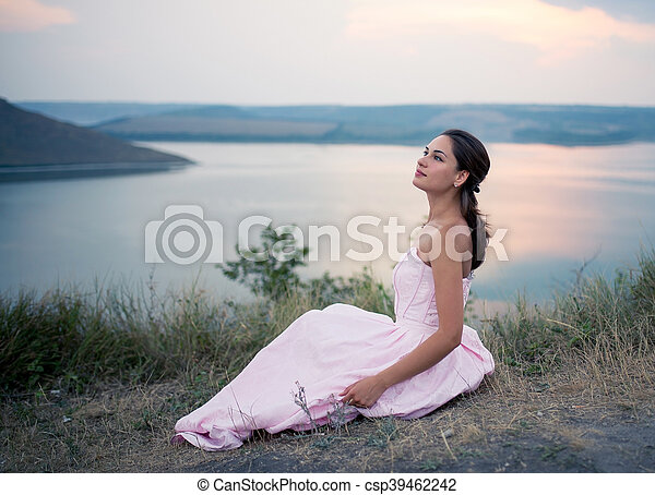 girl in a dress sitting on a rock by the river - csp39462242