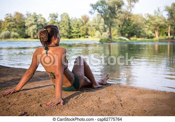 girl in a green bikini relaxing on the riverbank - csp62775764