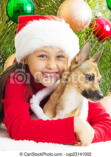 girl in a red Christmas dress hugging dog on the background of t - csp23141002