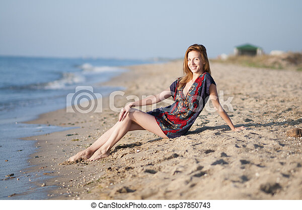 girl in a summer dress sitting on the beach - csp37850743