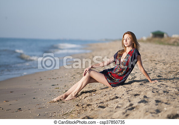 girl in a summer dress sitting on the beach - csp37850735