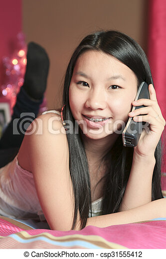 Girl in bedroom taling on the phone - csp31555412