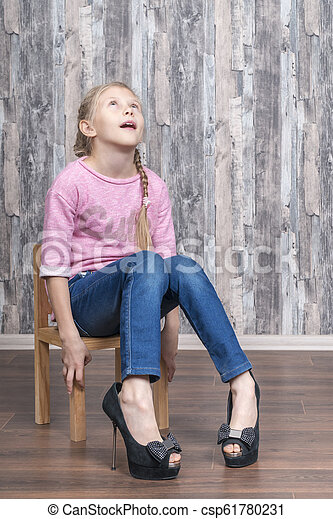 Girl in big shoes on the chair. Young